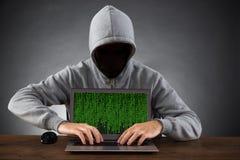 Hombre que corta el ordenador portátil en el escritorio Imagen de archivo libre de regalías