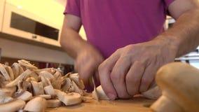 Hombre que corta setas de campo en la cocina Cocina aficionada en casa 4K se cierran encima del vídeo almacen de video