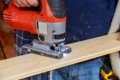 Hombre que corta un tablón con un tablero de madera que asierra de la máquina del rompecabezas fotografía de archivo