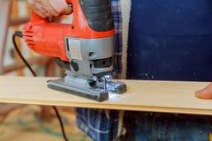 Hombre que corta un tabl?n con un tablero de madera que asierra de la m?quina del rompecabezas imagen de archivo