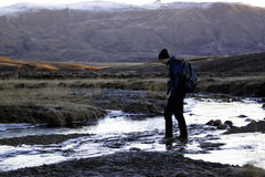 Hombre que cruza un río. Imagenes de archivo