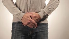 Hombre que cubre su uretra en dolor Problemas de los hombres en el fondo blanco Concepto MÉDICO almacen de video