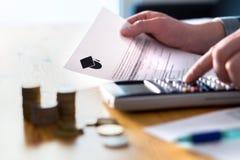 Hombre que cuenta el fondo de los ahorros de la universidad, la matrícula o el préstamo del estudiante imagen de archivo