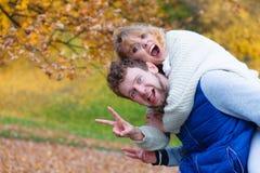 Hombre que da a cuestas paseo a la mujer en parque Fotos de archivo
