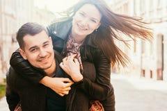 Hombre que da a cuestas paseo a su novia Pares felices en calle imagenes de archivo