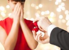 Hombre que da el anillo de diamante a la mujer en día de San Valentín foto de archivo