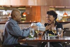 Hombre que da el regalo a la mujer en el restaurante Foto de archivo libre de regalías