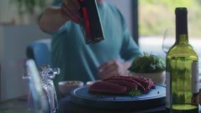 Hombre que da la botella del vinagre al amigo Ensalada de cuatro personas caucásicas de los amigos, filete y almuerzo italianos m almacen de metraje de vídeo