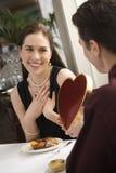 Hombre que da a la tarjeta del día de San Valentín de la mujer. imagenes de archivo