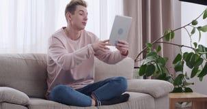Hombre que da los pulgares para arriba mientras que comunicación video en la tableta digital almacen de metraje de vídeo
