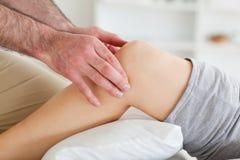 Hombre que da masajes a la rodilla de una mujer de mentira Fotos de archivo