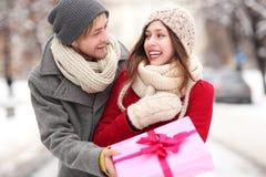 Hombre que da a mujer un regalo de la sorpresa Imagen de archivo