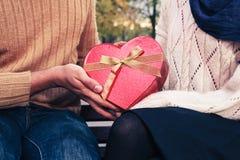 Hombre que da a mujer una caja en forma de corazón Imagen de archivo