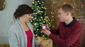 Hombre que da un anillo a la mujer cerca del árbol de navidad almacen de metraje de vídeo