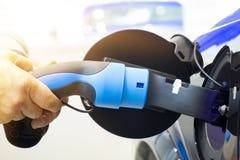 Hombre que da vuelta encendido a la carga del coche Coche de EV o coche eléctrico en la estación de carga imagen de archivo libre de regalías