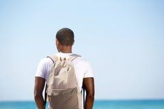 Hombre que defiende con la mochila el mar Imagenes de archivo