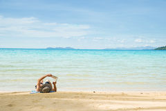 Hombre que descansa sobre la playa y el libro de lectura Imagen de archivo