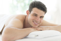 Hombre que descansa sobre la tabla del masaje en el balneario Fotografía de archivo libre de regalías
