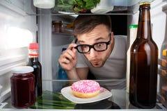 Hombre que descubre un buñuelo en el refrigerador Foto de archivo