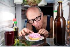 Hombre que descubre un buñuelo en el refrigerador Fotos de archivo