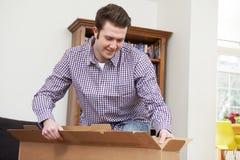 Hombre que desempaqueta la nueva televisión en casa fotos de archivo libres de regalías