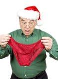 Hombre que desgasta el sombrero de Santa que sostiene las bragas rojas del cordón Imagen de archivo