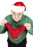 Hombre que desgasta el sombrero de Santa que sostiene las bragas rojas del cordón Imagen de archivo libre de regalías
