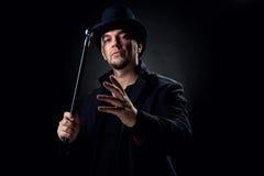 Hombre que desgasta el sombrero negro y la chaqueta dentro Imagen de archivo libre de regalías