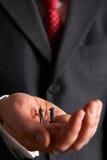 Hombre que detiene a Businessmen In Palm modelo de la mano fotos de archivo libres de regalías