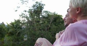 Hombre que detiene a la mujer en las manos en la terraza que habla, par joven que mira puesta del sol sobre bosque tropical almacen de video