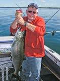 Hombre que detiene a rey grande Salmon Fish del lago Ontario fotos de archivo