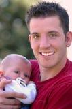 Hombre que detiene a un bebé Imágenes de archivo libres de regalías