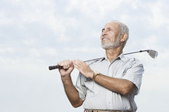 Hombre que detiene a un club de golf fotos de archivo libres de regalías
