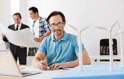 Hombre que dibuja un modelo de la central eléctrica de energía eólica Fotografía de archivo libre de regalías