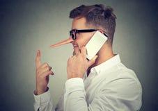 Hombre que dice mentiras mientras que teniendo llamada de teléfono imágenes de archivo libres de regalías