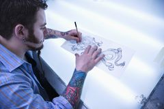 Hombre que diseña el tatuaje. Fotos de archivo