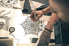 Hombre que diseña la imagen atractiva en la tabla Foto de archivo