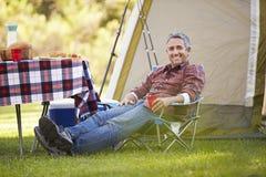 Hombre que disfruta de acampada en campo fotos de archivo