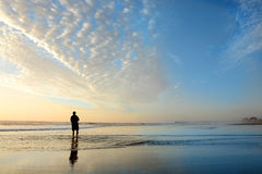 Hombre que disfruta de tiempo en la playa en la salida del sol Foto de archivo libre de regalías