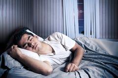 Hombre que duerme comfortablemente en su cama foto de archivo libre de regalías