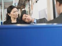 Hombre que duerme en el hombro de la empresaria en tren imagen de archivo libre de regalías