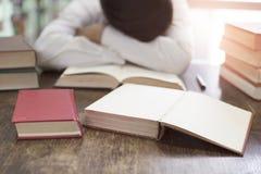 Hombre que duerme en el libro con la pila del libro de texto en el escritorio de madera Imagen de archivo