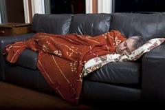 Hombre que duerme en el sofá imágenes de archivo libres de regalías