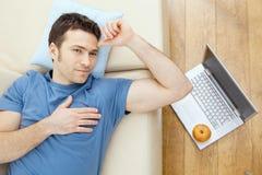Hombre que duerme en el sofá Foto de archivo libre de regalías