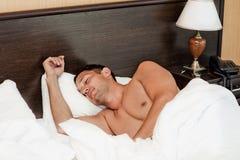Hombre que duerme en la cama en el país Imagen de archivo