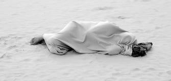 Hombre que duerme en la playa del mar foto de archivo