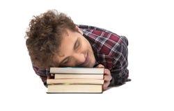 Hombre que duerme en la tabla con los libros Fotos de archivo libres de regalías