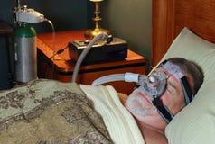 Hombre que duerme (vista delantera) con CPAP y oxígeno imagenes de archivo
