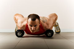Hombre que ejercita con pesas de gimnasia Fotografía de archivo