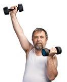 Hombre que ejercita con pesas de gimnasia Fotografía de archivo libre de regalías